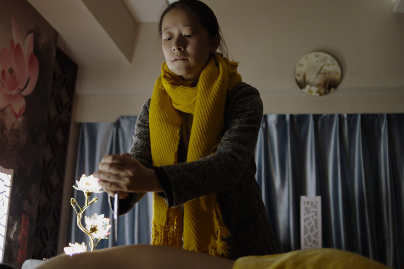 A young woman holding sharp tool with both hands pointing at back of a man lying down - Lost Lotus - THIS Buddhist Film Festival