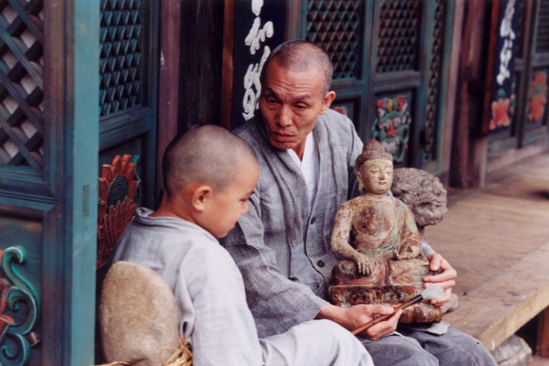 An old monk holding a Buddha statue talking to a child monk - Spring Summer Fall Winter and Spring - THIS Buddhist Film Festival