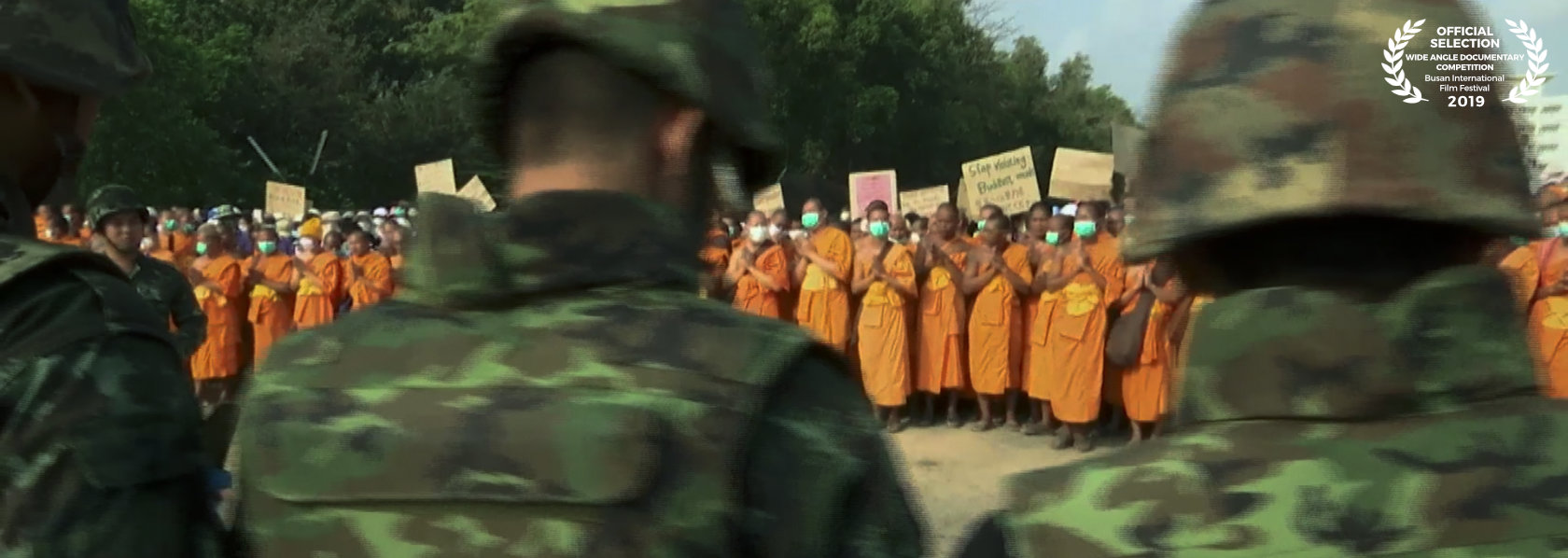 Buddhist monks holding placards in front of military - Come and See - THIS Buddhist Film Festival
