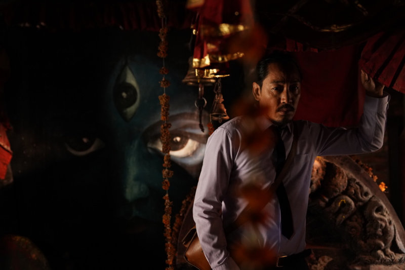 Man stands in front of painting of three eyed goddess - Looking for a Lady With Fangs and a Moustache - THIS Buddhist Film Festival