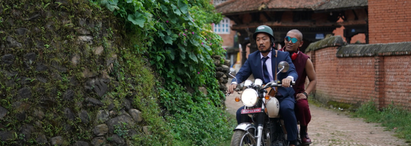 Man in suit and monk wearing sunglasses ride a motorcycle - Looking for a Lady With Fangs and a Moustache - THIS Buddhist Film Festival