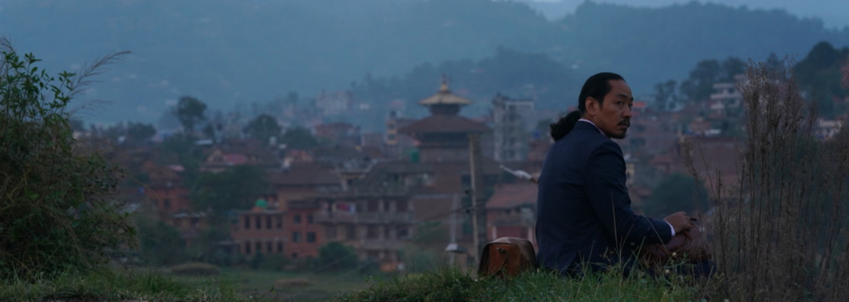 Man with ponytail sits on hill overlooking mountaineous town - Looking for a Lady With Fangs and a Moustache - THIS Buddhist Film Festival