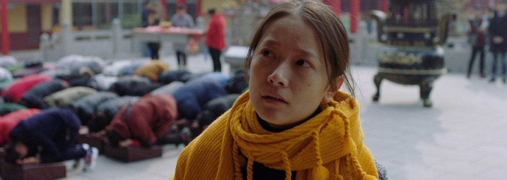 A young woman looking with eyes to her right with people kneeing down in prayers on background - Lost Lotus - THIS Buddhist Film Festival