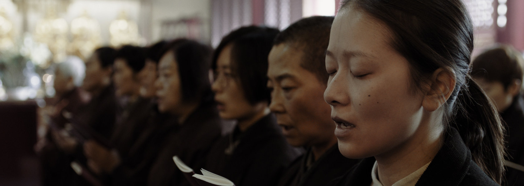 A young woman hold a chanting book with palms together with other laypeople - Lost Lotus - THIS Buddhist Film Festival