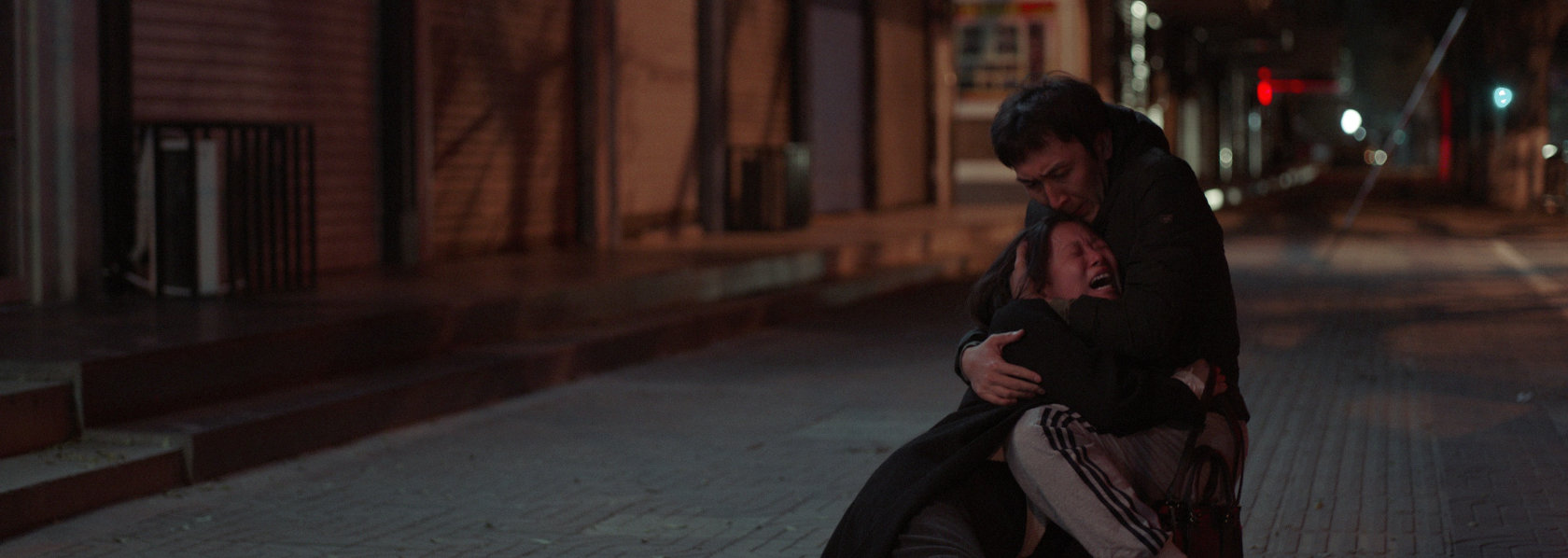 A man kneeling on the floor hugging a wailing woman in the street - Lost Lotus - THIS Buddhist Film Festival