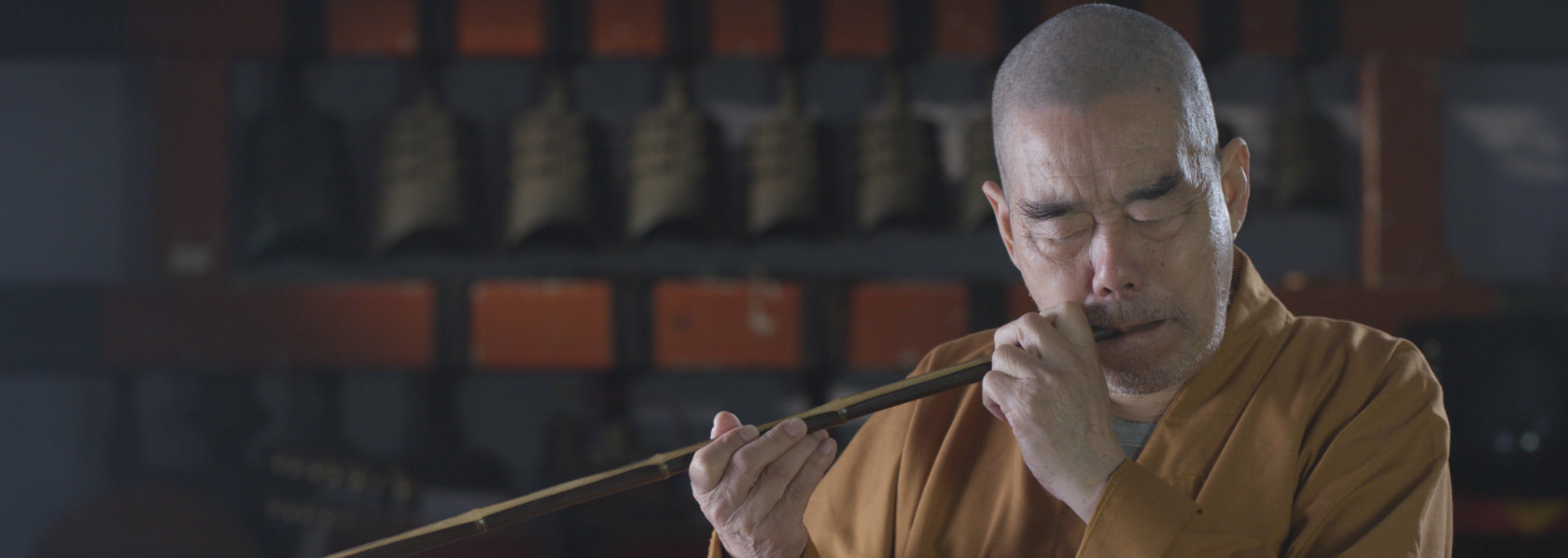 Elderly monk playing wind instrument - Music Monks - THIS Buddhist Film Festival