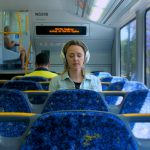 Lady wearing headphones in a train - My Year of Living Mindfully - THIS Buddhist Film Festival