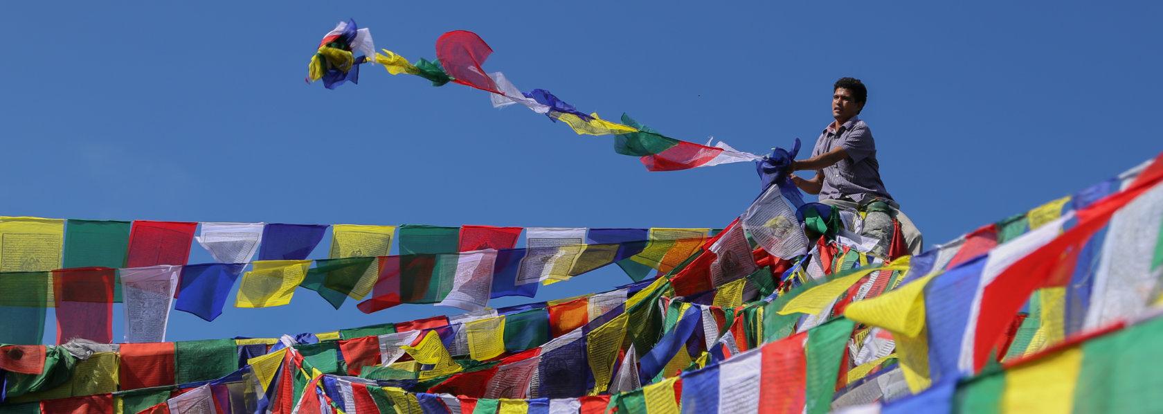 A man sitting high up throwing a string of buddhist flags - Precious Guru - THIS Buddhist Film Festival