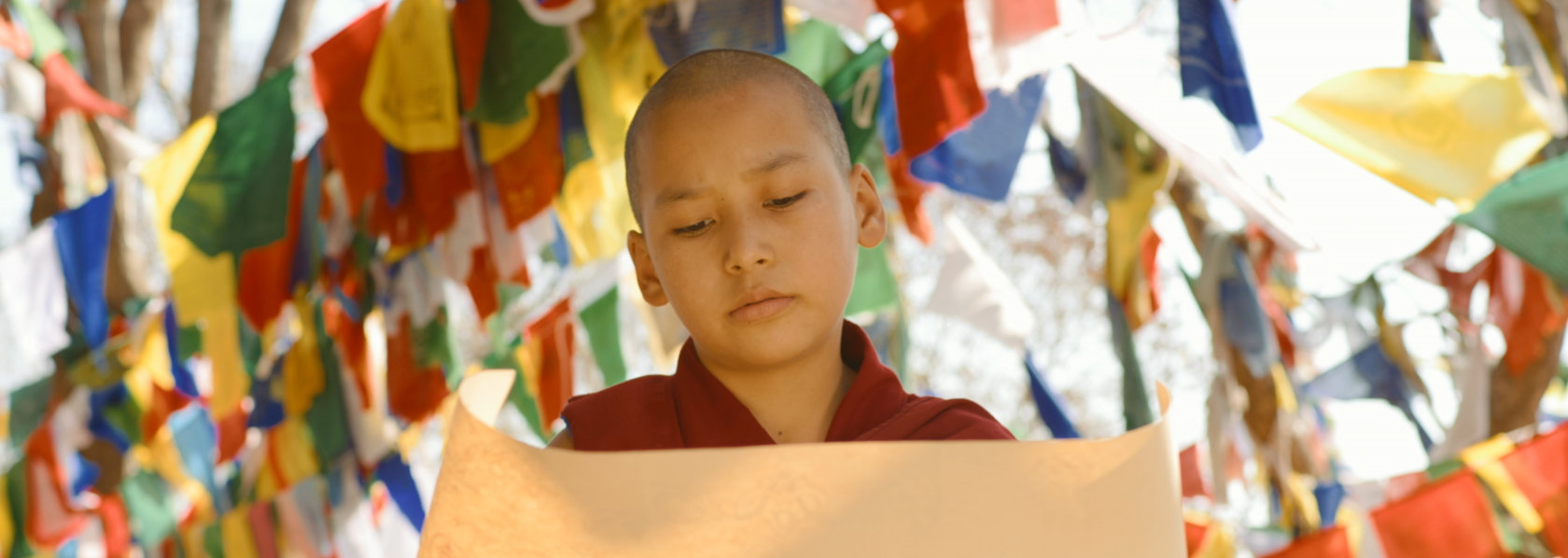 Young monk looking at paper background tibetan prayer flags - Saffron Heart - THIS Buddhist Film Festival