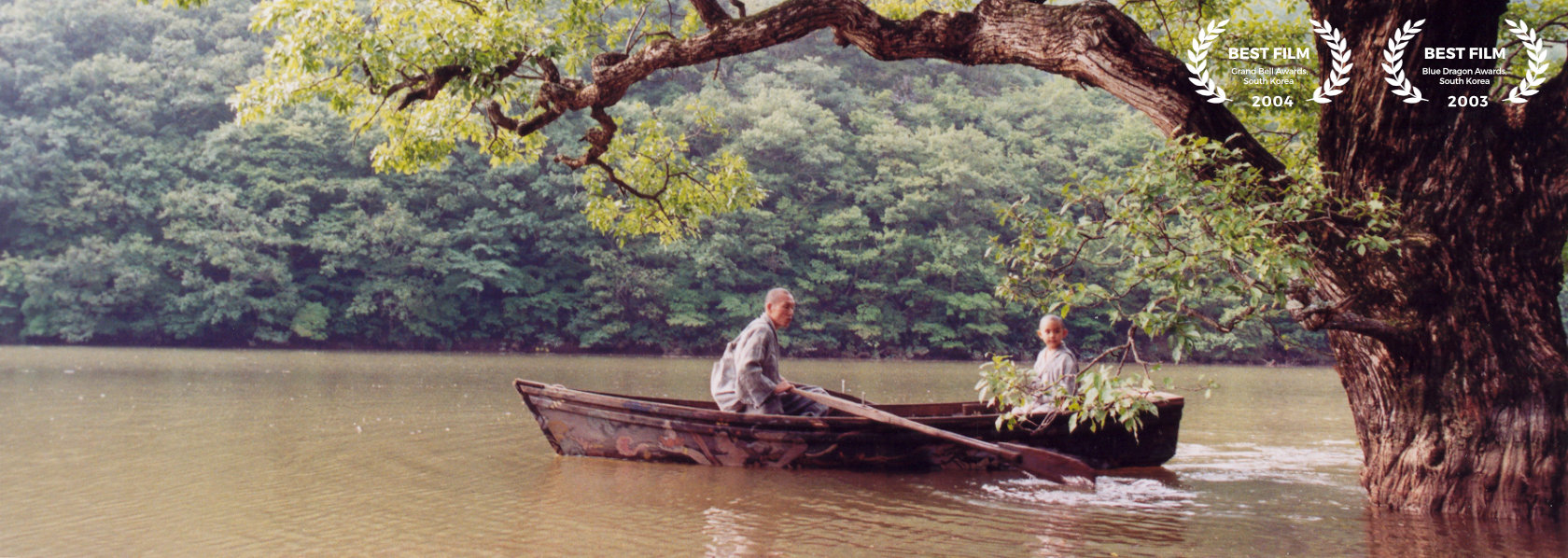 A young monk rowing a boat with a child monk sitting on the oppposite side - Spring Summer Fall Winter and Spring - THIS Buddhist Film Festival