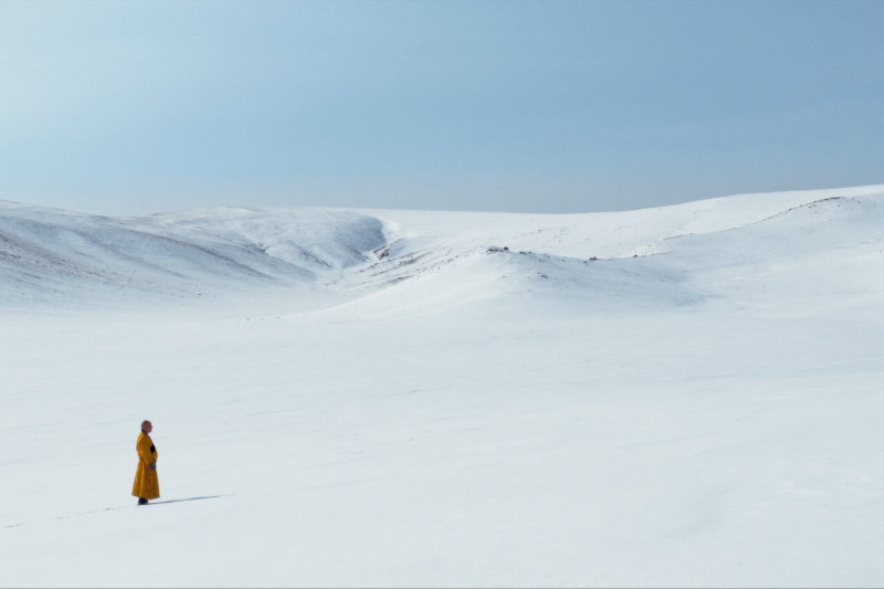 The lama standing in snow winter mountain background - The Medicine Buddha - THIS Buddhist Film Festival