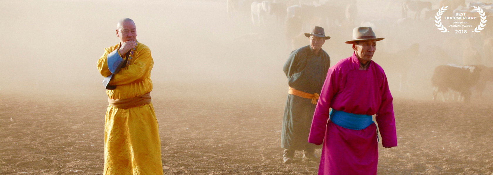 The lama in yellow robes looking at a mongolian man in fuscia clothes blue belt - The Medicine Buddha - THIS Buddhist Film Festival