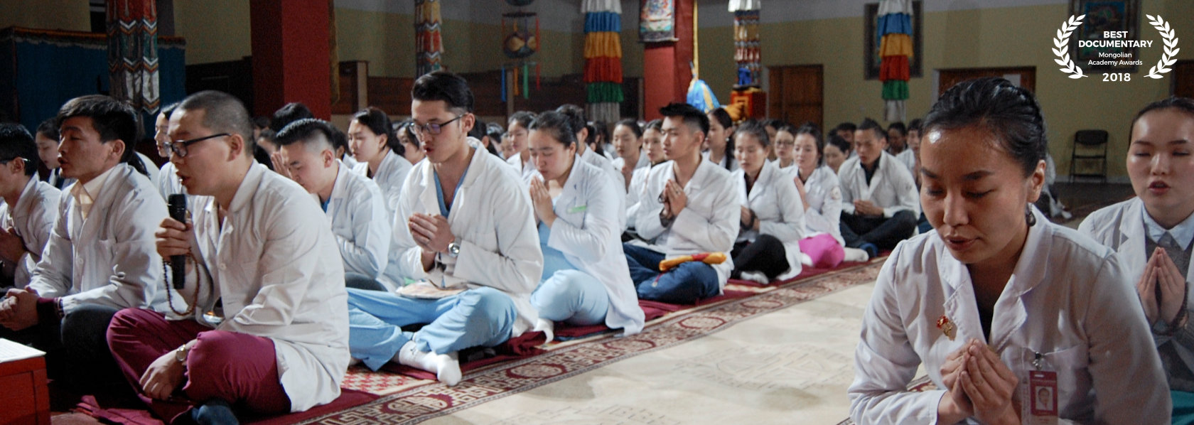 A group of people with palms together in prayer session - The Medicine Buddha - THIS Buddhist Film Festival