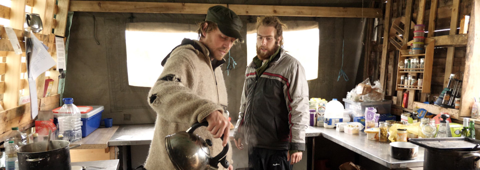 Two men making tea in a wooden cabin - The Way Out - THIS Buddhist Film Festival