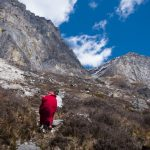 Backview of person in red robes and hat walking up a mountain - Wandering But Not Lost - THIS Buddhist Film Festival