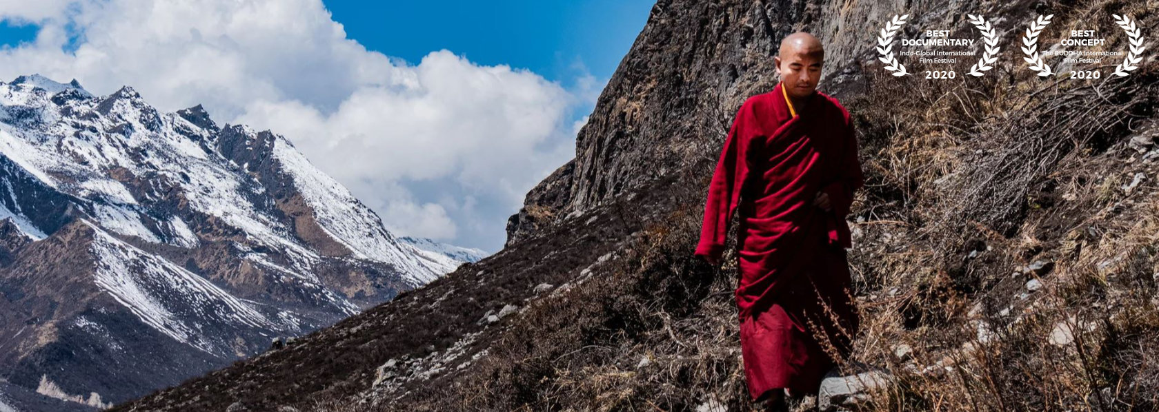 Mingyur Rinpoche looking down walking on a mountain with winter mountain blue sky background - Wandering But Not Lost - THIS Buddhist Film Festival