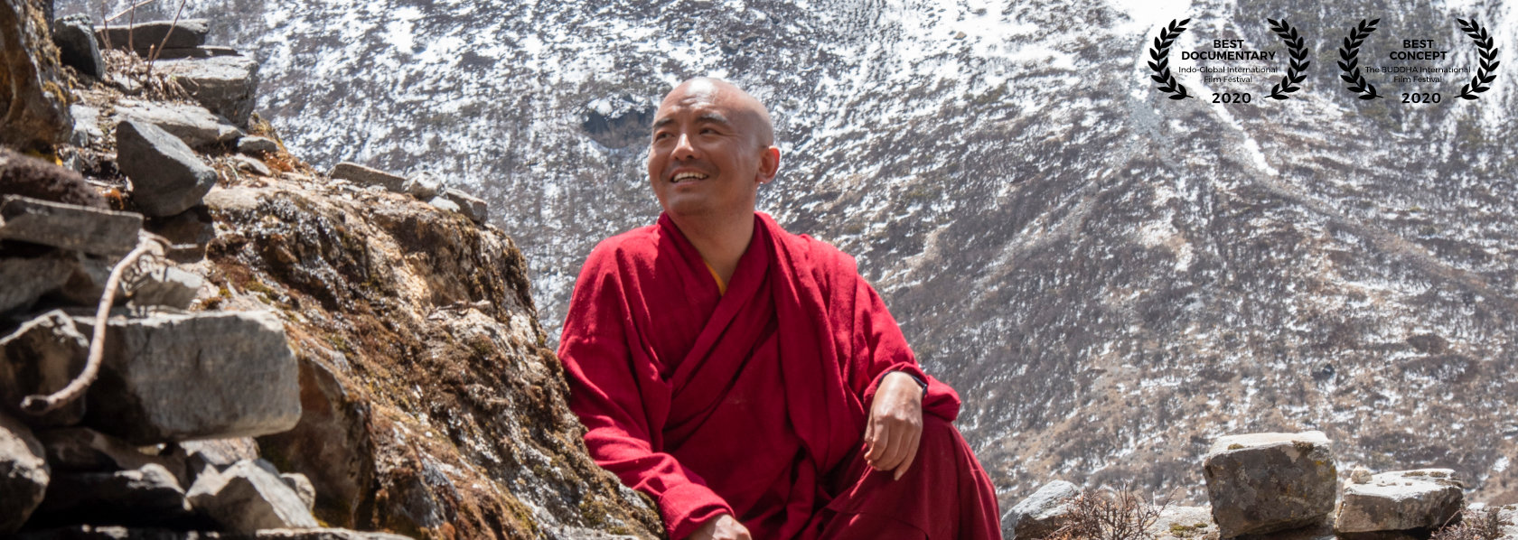 Mingyur Rinpoche smiling looking to his right sitting with one knee up winter mountain background - Wandering But Not Lost - THIS Buddhist Film Festival