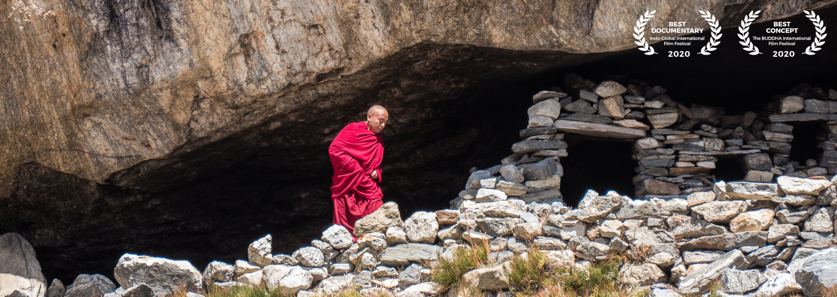 Mingyur Rinpoche walking beside a mountain with stones - Wandering But Not Lost - THIS Buddhist Film Festival